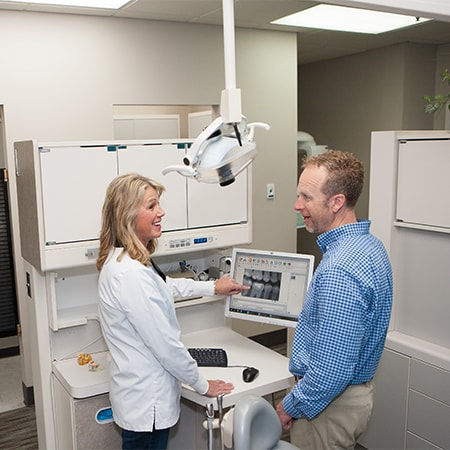 Fishers Indiana dentist, Dr. Marie Holt, talking to a patient about his smile.