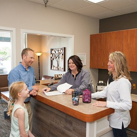 Dr. Holt, dentist in Fishers Indiana dentist office welcoming a young patient and her dad