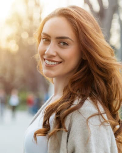 A red haired woman smiling about cosmetic dentistry in Fishers, IN