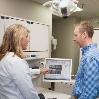 Dr. Holt discussing white fillings with a patient while looking at his x-ray